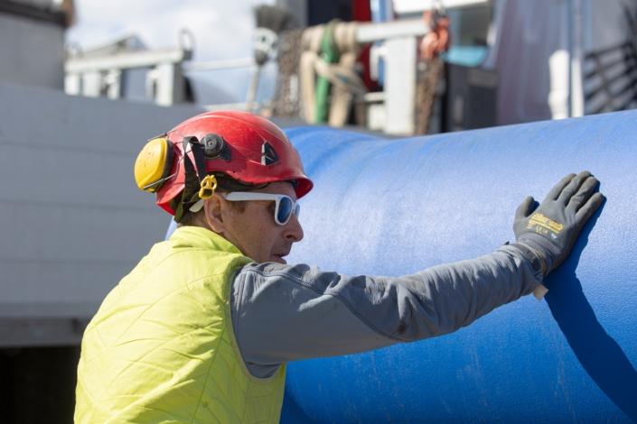 ouvrier en train d'inspecter un tuyau