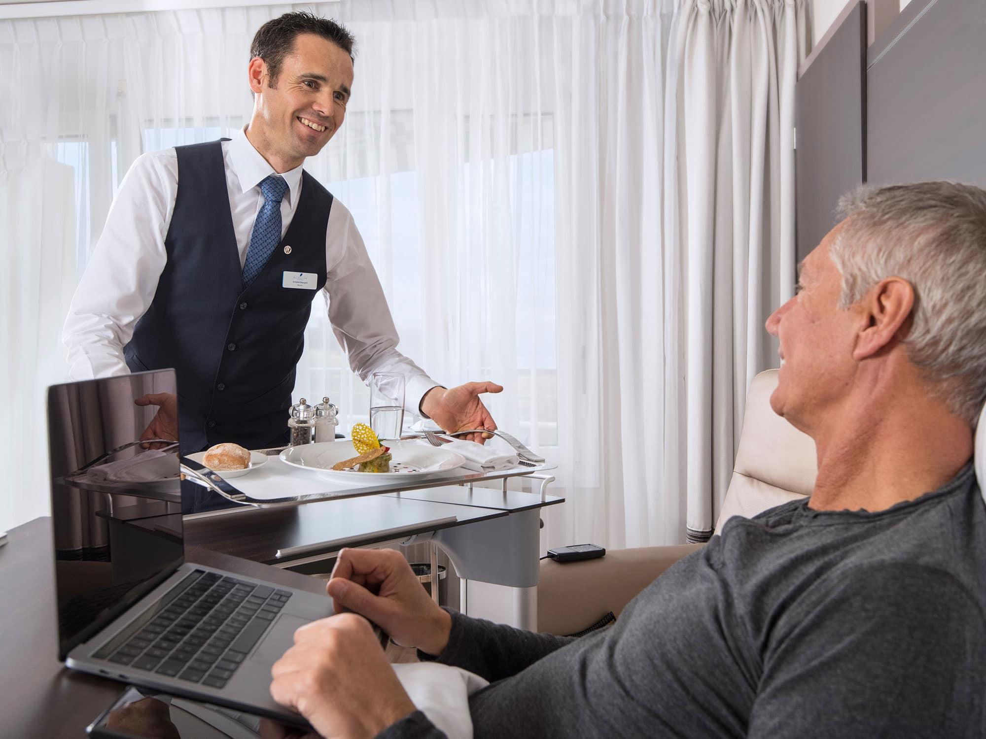 Un patient se fait servir le repas dans une clinique privée, image servant à souligner la photo corporate