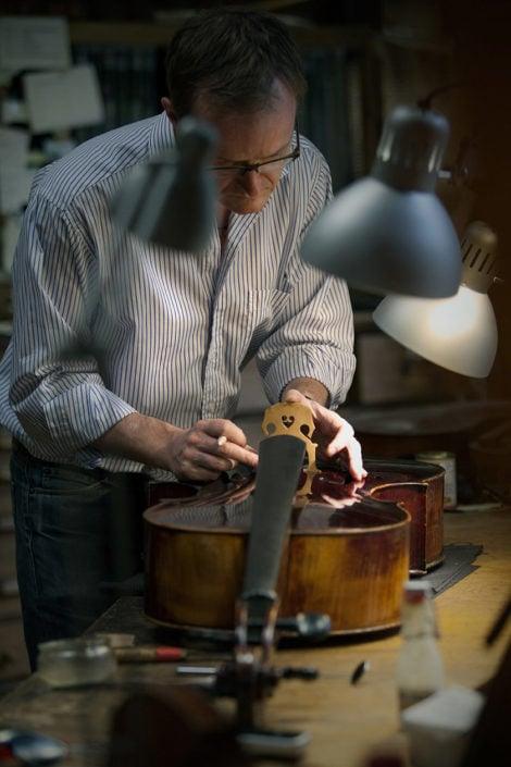 artisan en train de réparer un violon dans son atelier