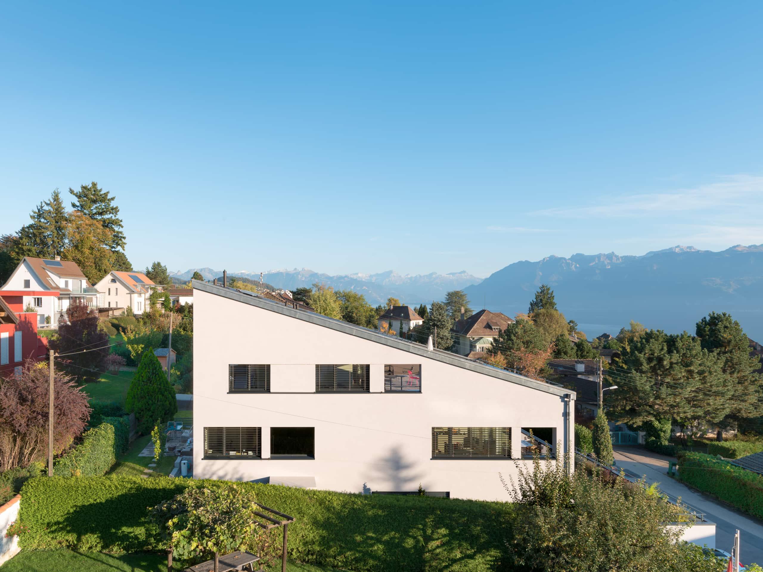 maison avec toit se confondant aux Alpes